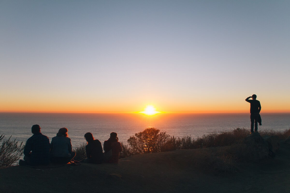 peoples on hill near ocean at golden hour
